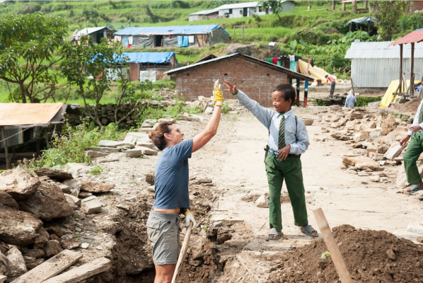 Frau gibt Kind High Five in Nepal