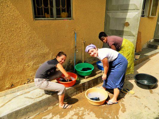 Drei Frauen waschen Wäsche in Schalen in Uganda