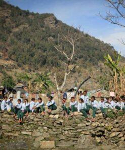 Kinder sitzen auf Steinmauer in Swaragau