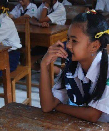 Mädchen mit Zöpfen und gelber Schleife in der Schule