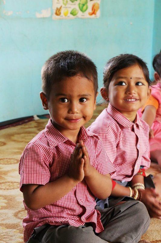 Junge faltet die Hände und Mädchen lächelt im Hintergrund