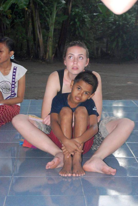 Volontärin sitzt mit Kind am Boden