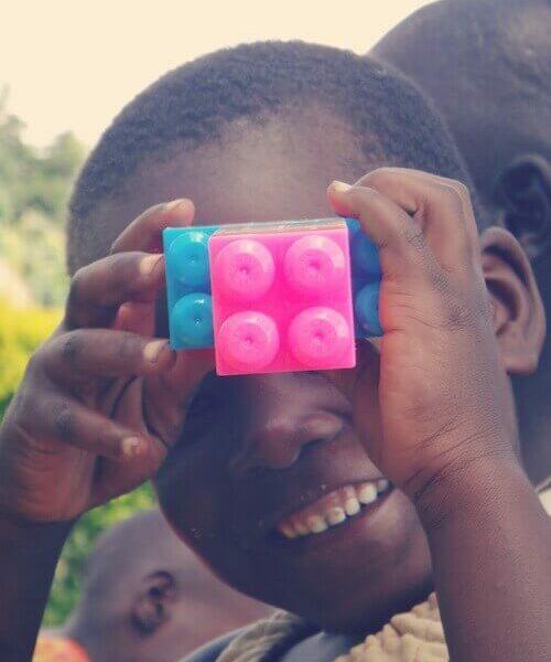 Kind hält sich einen blauen und einen rosaroten Legostein vor das Gesicht