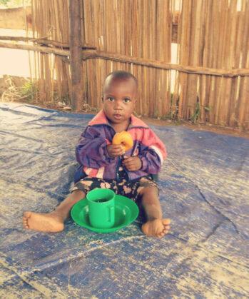 Kind sitzt auf dem Boden mit grüner Tasse und grünem Teller und isst Donut
