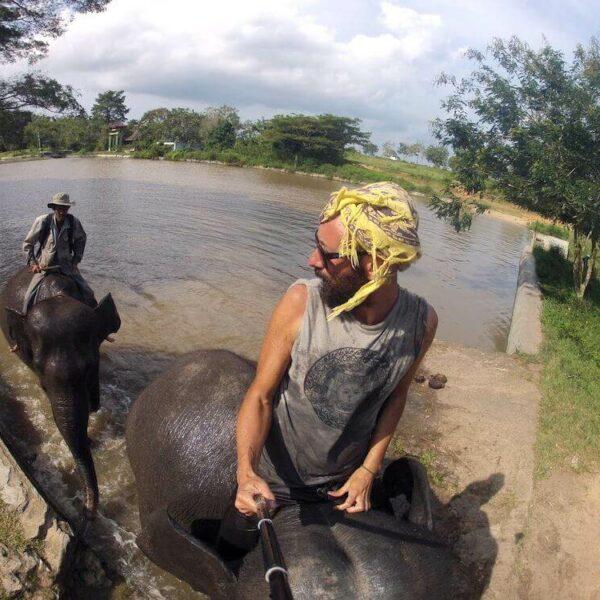 Zwei Männer reiten auf zwei Elefanten durchs Wasser