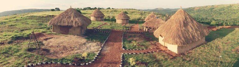 Kleine Hütten mit Strohdächern und einer Feuerstelle