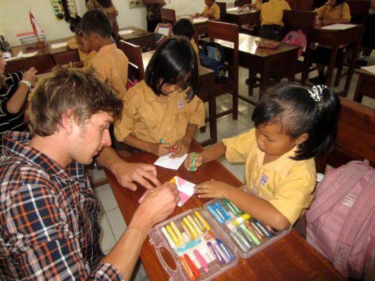 Volontär mit zwei Kindern und bunten Stiften