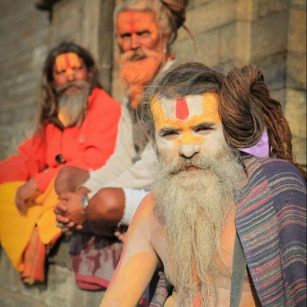 Drei Männer mit langen Haare und Bärten und bunten Bemalungen im Gesicht