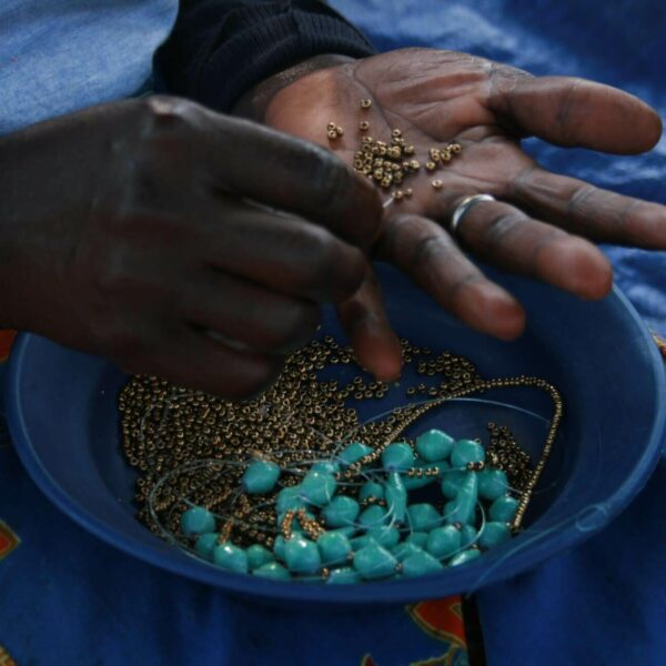 Goldene und türkise Perlen werden zu einer Kette aufgefädelt