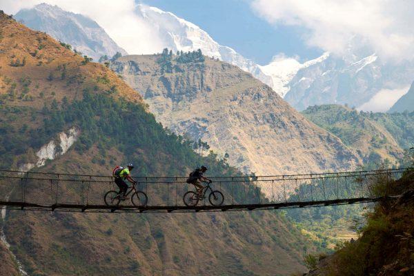 Zwei Radfahrer fahren über eine Hängebrücke