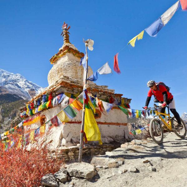 Fahrradfahrer fährt an bunten Gebetsfahnen vorbei