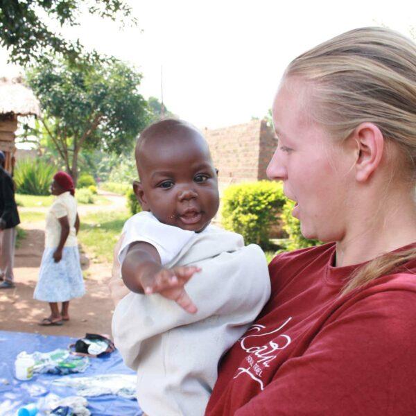 Volontärin mit Kind auf dem Arm