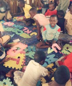 Viele Kinder spielen auf dem Boden mit Schaumstoffbuchstaben
