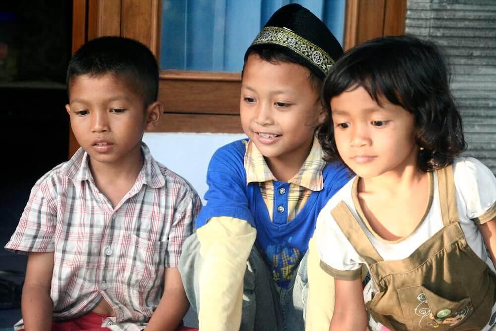 Drei Kinder schauen auf etwas