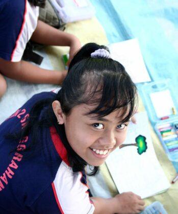 Lachendes Kind mit einem gemalten Baum