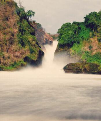 Wasserfall zwischen zwei Gebirgszügen und Wald