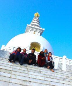 Reisegruppe sitzt auf den Stufen vor einem Tempel