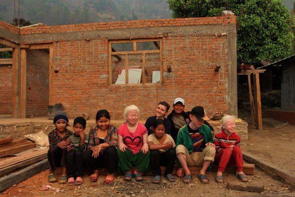 Kinder sitzen vor Baustelle in Swaragau
