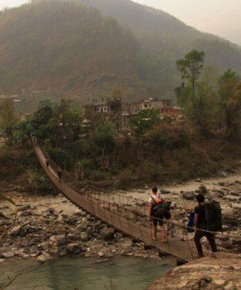 Reisende gehen über Hängebrücke