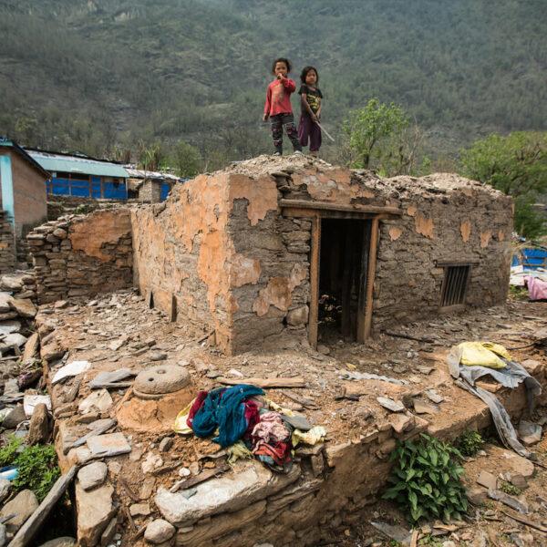 Zwei Kinder stehen auf einem zerstörten Haus
