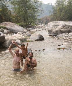 Zwei Männer baden mit Kind im Fluss
