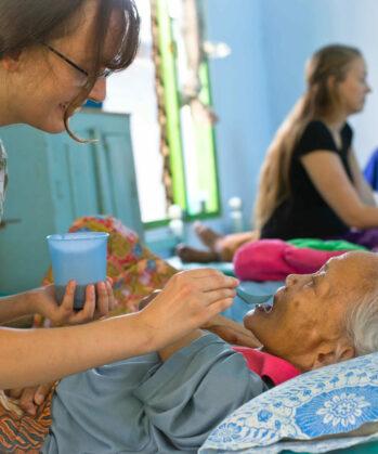 Voluntärin beim füttern einer pflegebedürftigen alten Frau