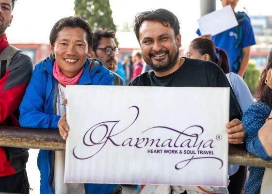 Bhagwan und Guide Jagat halten ein Karmalaya-Schild auf der Leadership-Journey