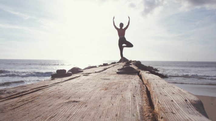 Mann beim Yoga auf einem Steg