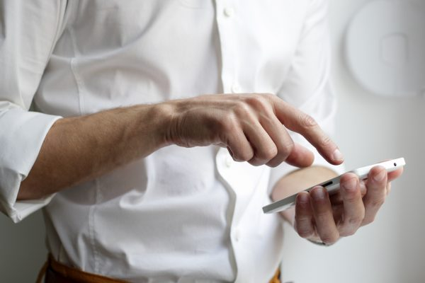 Mann mit Handy im weißen Hemd