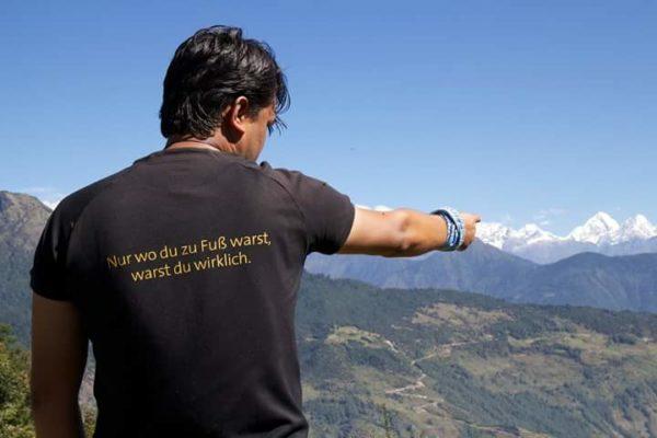 Karmalaya Reisender zeigt auf Berge in Helambu-Region Nepal