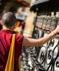 Mönch berührt Gebetsmühlen in Nepallen