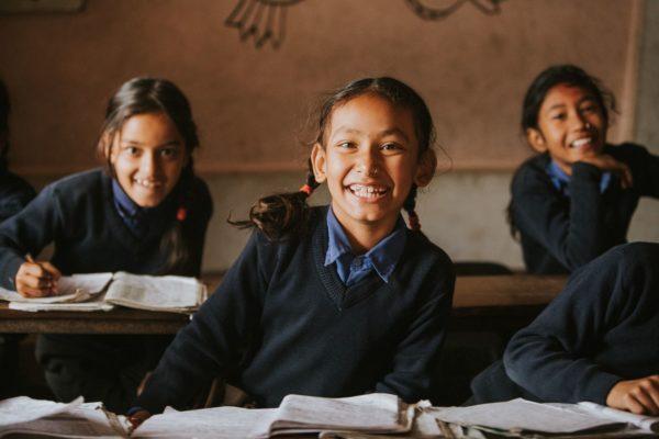 Lächelnde Schulmädchen sitzen im Klassenzimmer in Indonesien