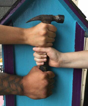 Drei Volunteer-Hände umfassen Hammer