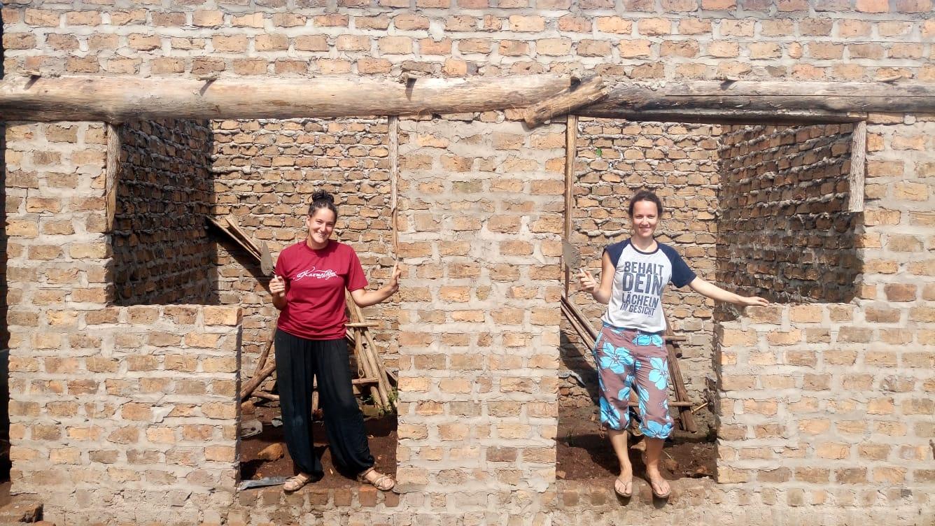 Zwei Volontärinnen stehen in neuem Haus in Uganda