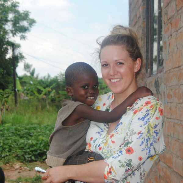 Volontärin mit fröhlichem Kind in Uganda