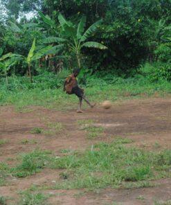 Ugandisches Kind schießt mit Fußball