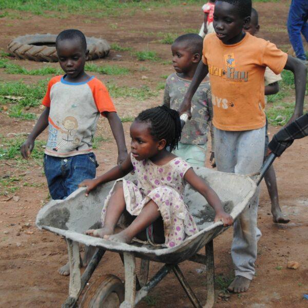 Kinder in Uganda spielen mit Schubkarren