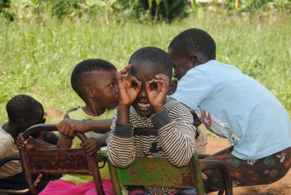 Kind aus Uganda formt Brille mit Händen