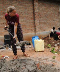Volontärin mit Schaufel hilft in einem Bau-Workcamp in Uganda
