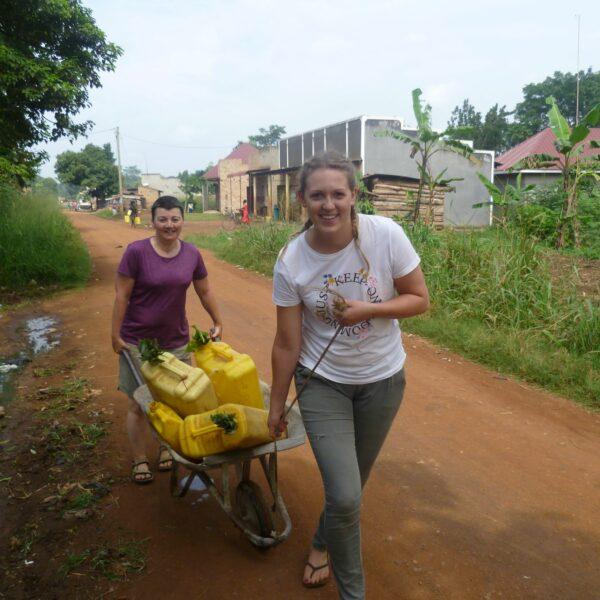 Freiwillige transportieren Wasserkanister in Uganda