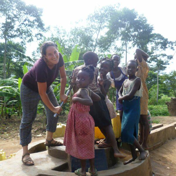 Freiwillige und Kinder beim Brunnen in Uganda