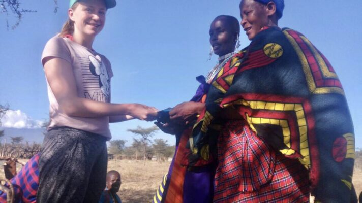 Participant giving card to Maasai people