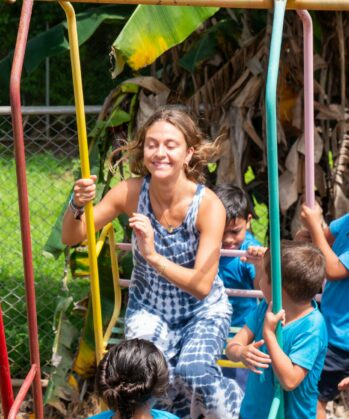 Volontärin schaukelt mit Kinder aus dem Projekt