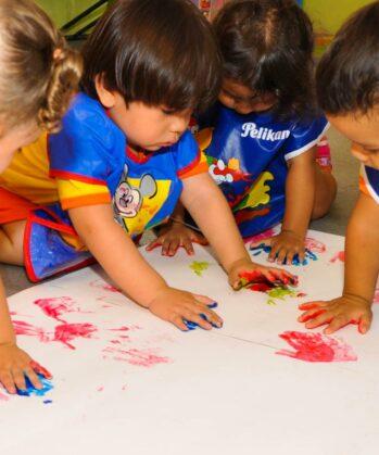 Kinder machen Handabdruck auf großes Papier