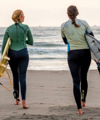 Zwei Frauen mit Surfbrett unter den Armen
