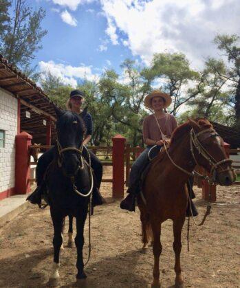 Zwei Volontärinnen reiten Pferd